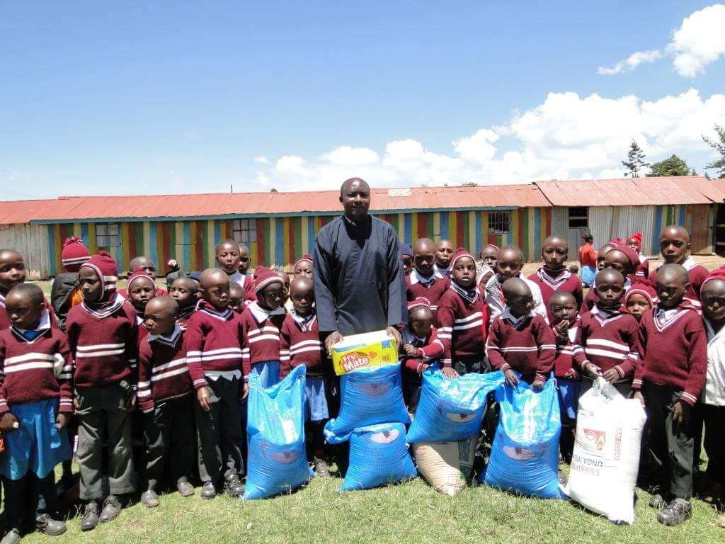 Orthodox priest in Kenya receiving food donations for children children